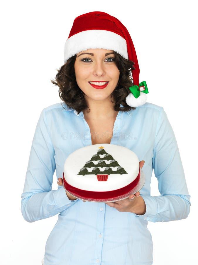 Mujer joven en Santa Hat Holding una torta de la fruta de la Navidad imagen de archivo libre de regalías