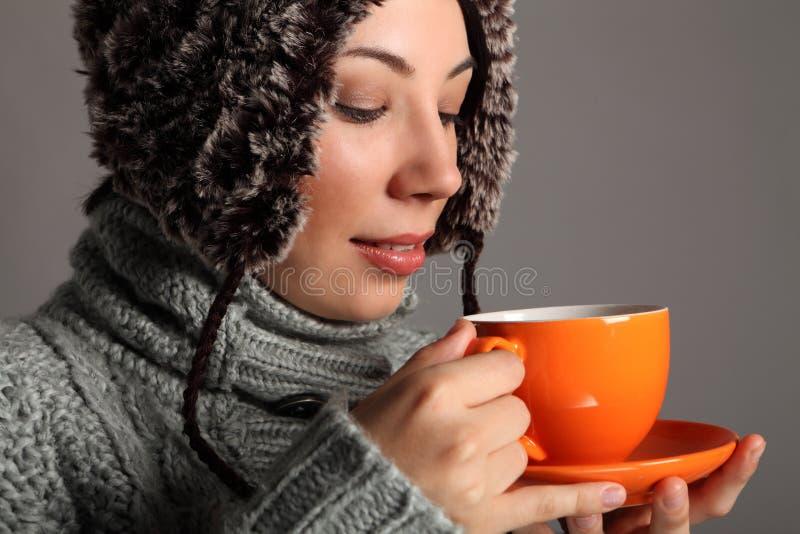 Mujer joven en sombrero caliente del invierno que bebe té caliente fotografía de archivo