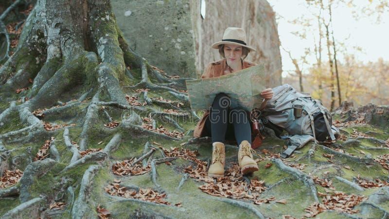 Mujer joven en sombrero elegante y la camisa que miran al mapa turístico, después mirando alrededor outdoors imágenes de archivo libres de regalías