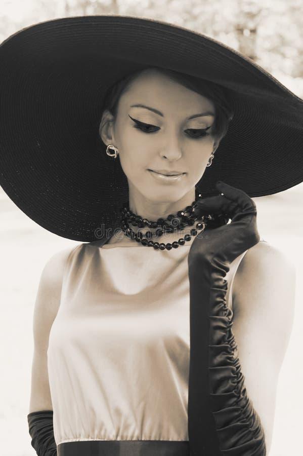 Mujer joven en sombrero negro imagenes de archivo