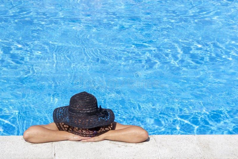 Mujer joven en sombrero negro que disfruta de bronceado en piscina Ocio del día de fiesta en día soleado feliz Concepto de las va foto de archivo libre de regalías