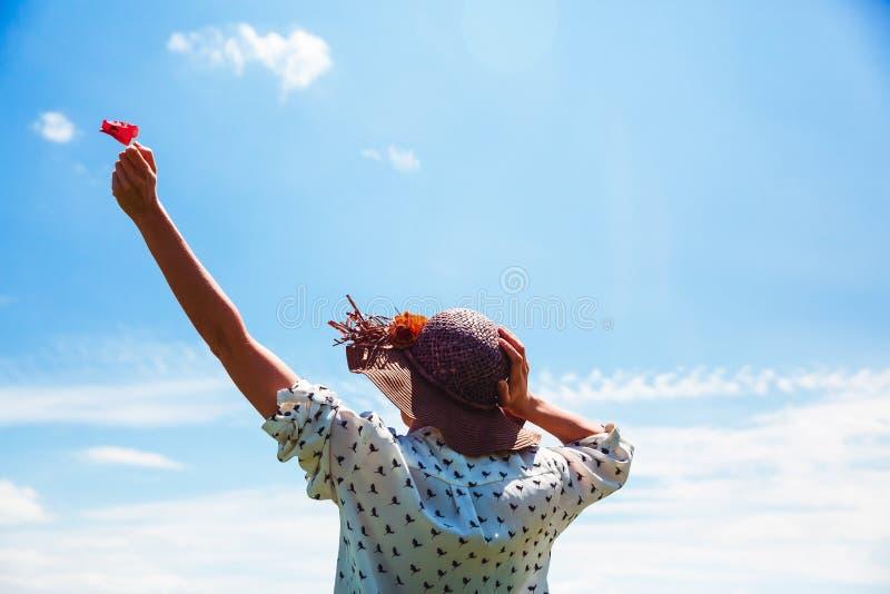 Mujer joven en sombrero que disfruta del tiempo de verano que detiene a una muchacha al aire libre de la sonrisa del cielo azul d foto de archivo libre de regalías