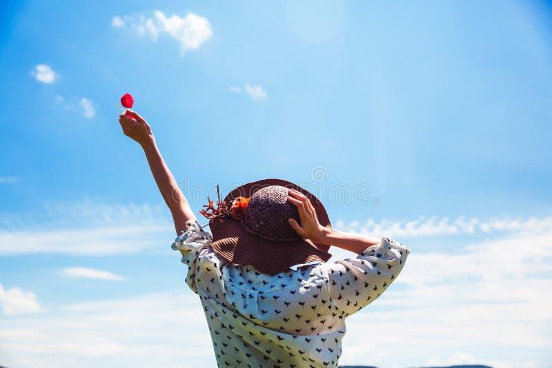 Mujer joven en sombrero que disfruta del tiempo de verano que detiene a una muchacha al aire libre de la sonrisa del cielo azul d foto de archivo