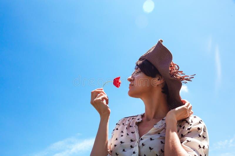 Mujer joven en sombrero que disfruta del tiempo de verano que huele una sonrisa al aire libre del cielo azul de las vacaciones de fotos de archivo