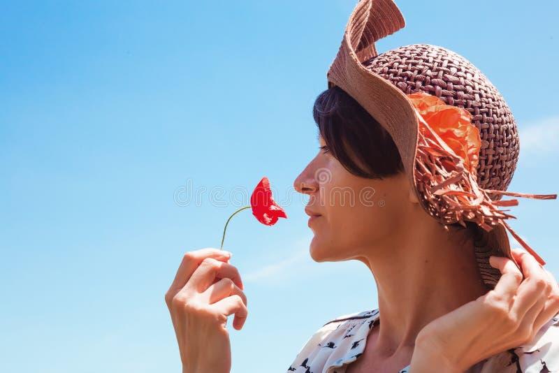 Mujer joven en sombrero que disfruta del tiempo de verano que huele una sonrisa al aire libre del cielo azul de las vacaciones de fotografía de archivo