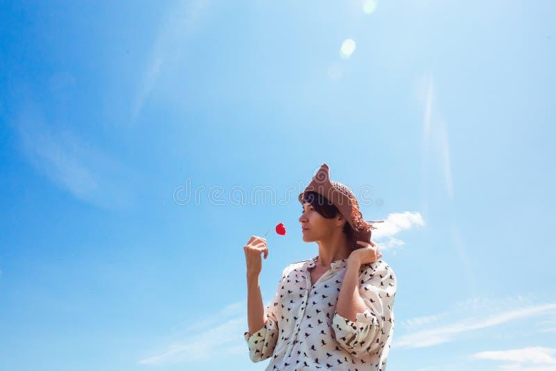 Mujer joven en sombrero que disfruta del tiempo de verano que huele una sonrisa al aire libre del cielo azul de las vacaciones de foto de archivo libre de regalías
