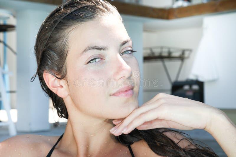 mujer joven en su mano de la terraza del hogar de la piscina debajo de la barbilla imágenes de archivo libres de regalías