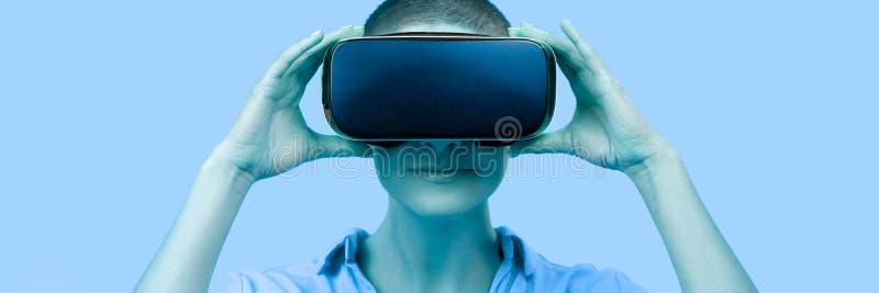 Mujer joven en su 30s usando gafas de la realidad virtual Mujer que lleva las auriculares de VR aisladas sobre bandera azul Exper imagenes de archivo