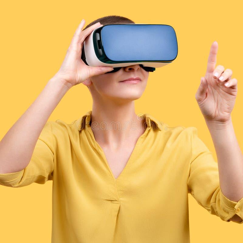 Mujer joven en su 30s usando gafas de la realidad virtual Mujer que lleva los vidrios de VR aislados sobre fondo amarillo imagen de archivo