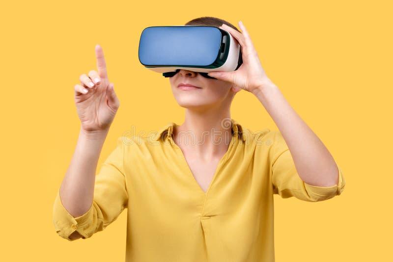 Mujer joven en su 30s usando gafas de la realidad virtual Mujer que lleva los vidrios de VR aislados sobre fondo amarillo Experie imagen de archivo libre de regalías