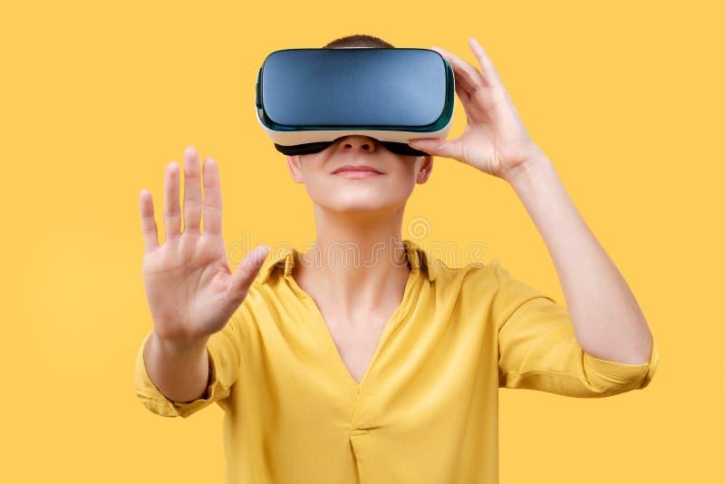 Mujer joven en su 30s usando gafas de la realidad virtual Mujer que lleva los vidrios de VR aislados sobre fondo amarillo Experie foto de archivo