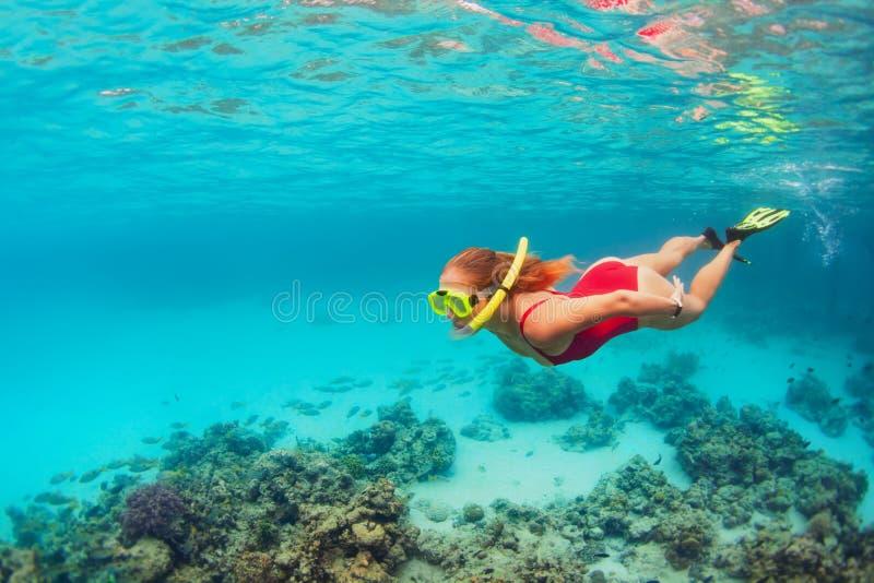 Mujer joven en submarino de la zambullida de la máscara que bucea con los pescados tropicales imagenes de archivo