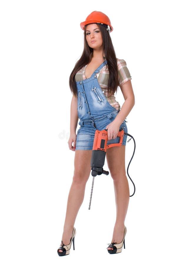 Mujer joven en taladro de martillo eléctrico de la bruja de los vaqueros Aislado fotos de archivo libres de regalías