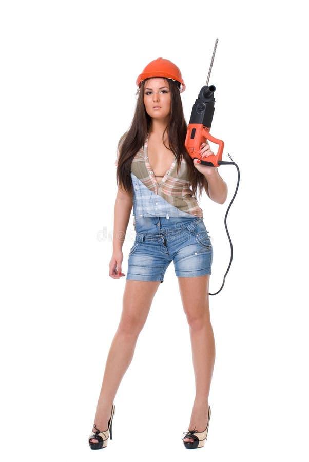 Mujer joven en taladro de martillo eléctrico de la bruja de los vaqueros Aislado foto de archivo
