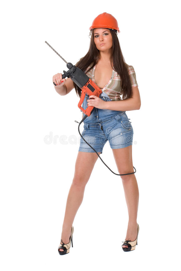 Mujer joven en taladro de martillo eléctrico de la bruja de los vaqueros Aislado imagen de archivo