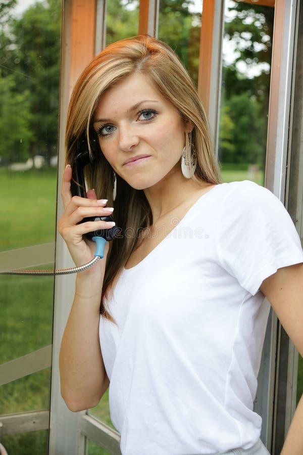 Mujer joven en teléfono público imágenes de archivo libres de regalías
