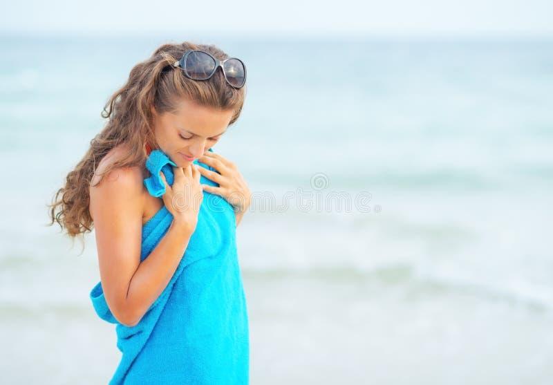 Mujer joven en toalla en la playa fotos de archivo