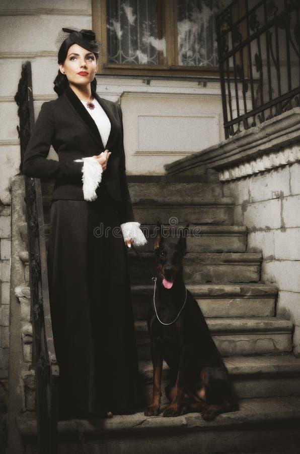 Mujer joven en traje antiguo con el perro (ver antiguo) fotos de archivo libres de regalías