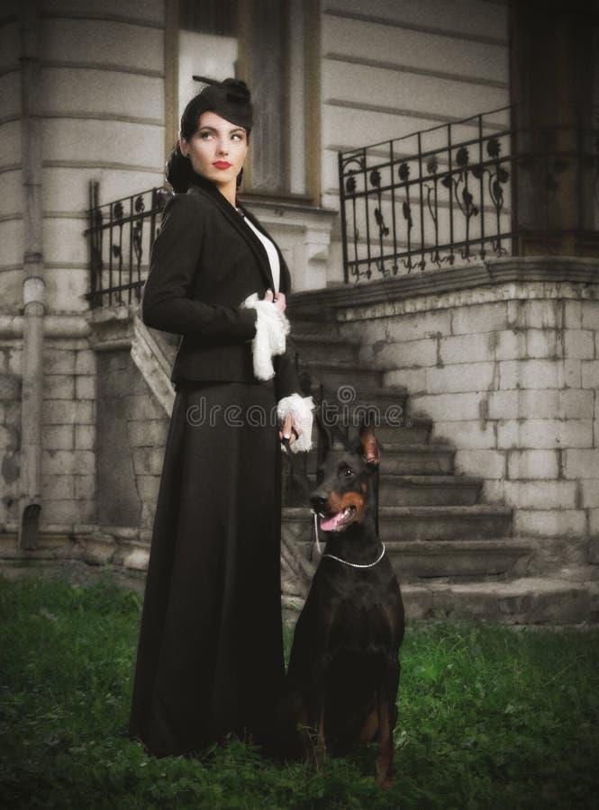 Mujer joven en traje antiguo con el perro (ver antiguo) imagen de archivo