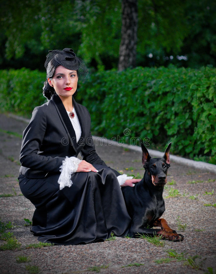 Mujer joven en traje antiguo con el perro (ver normal) imagen de archivo libre de regalías