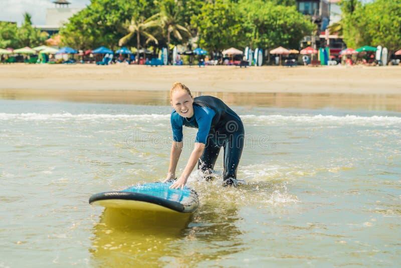 Mujer joven en traje de baño con la resaca para los principiantes listos para practicar surf P imagen de archivo