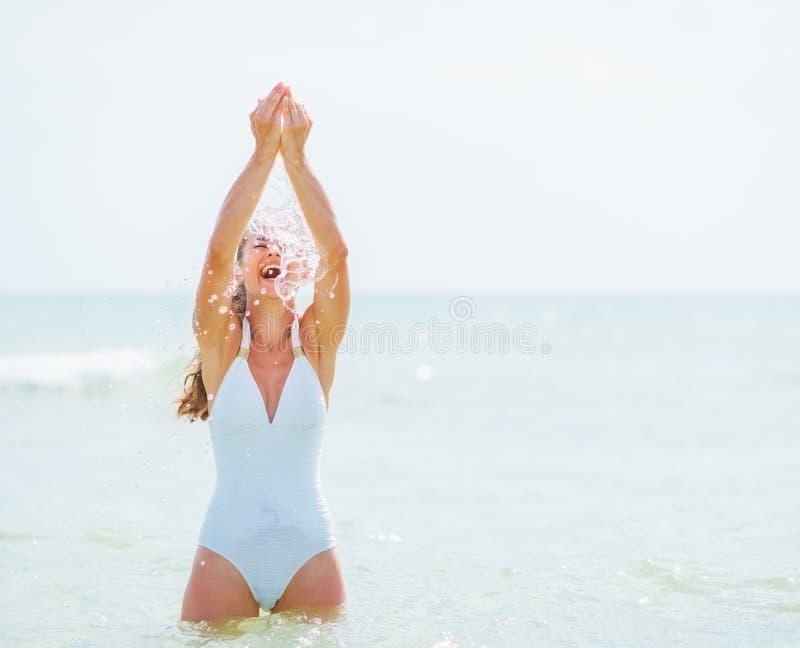 Mujer joven en traje de baño que goza de la agua de mar fotografía de archivo libre de regalías