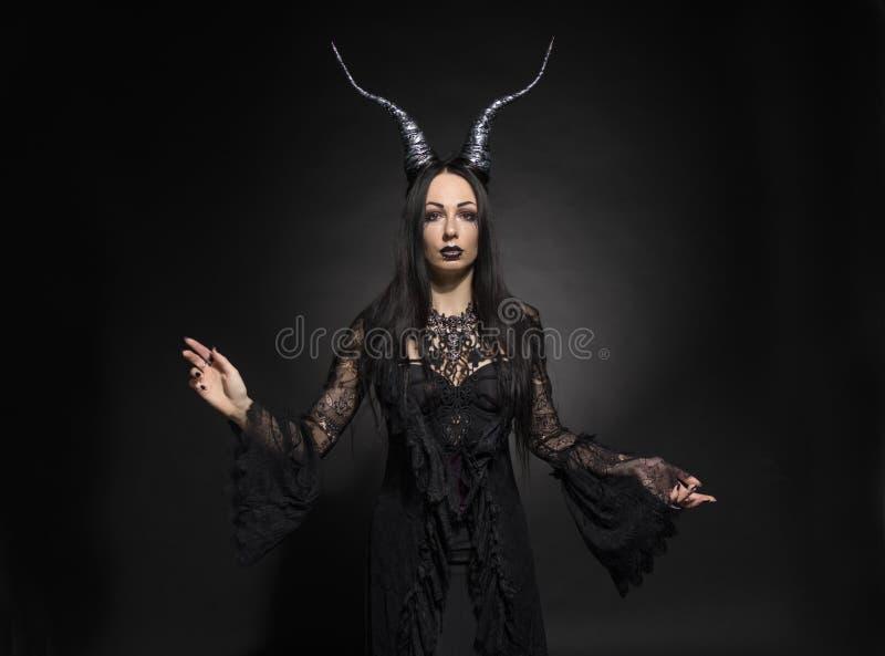Mujer joven en traje negro de la fantasía imagen de archivo