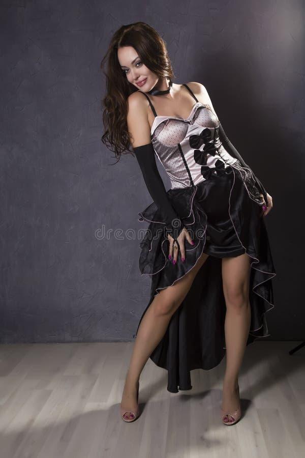 Mujer joven en un baile español del vestido en un fondo gris imagen de archivo libre de regalías
