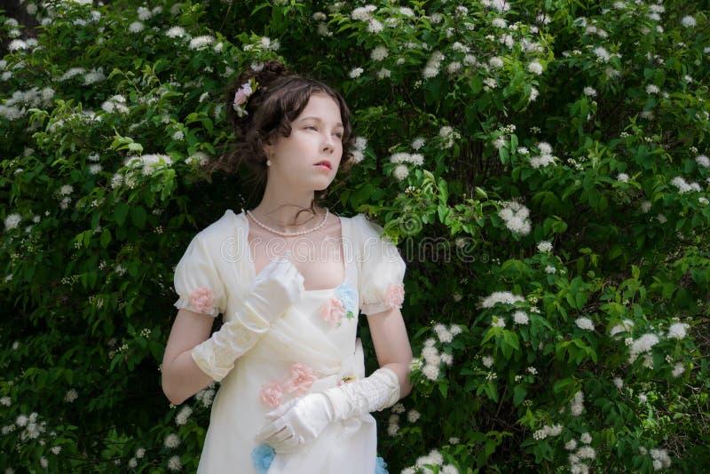 Mujer joven en un blanco de vestido largo elegante en flores fotos de archivo libres de regalías