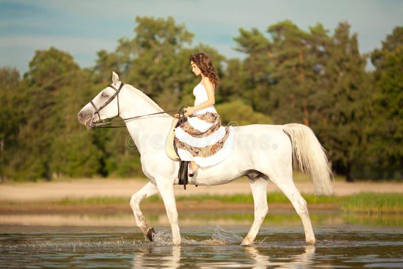 Mujer joven en un caballo Jinete de lomo de caballo, caballo de montar a caballo de la mujer en b imagen de archivo libre de regalías