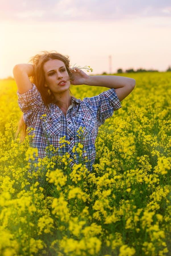 Mujer joven en un campo de la rabina del aceite en la floración en puesta del sol Concepto de la libertad y de la ecología fotografía de archivo libre de regalías