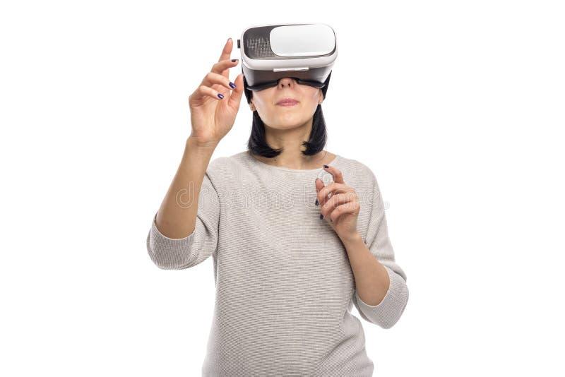 Mujer joven en un casco de la realidad virtual en un blanco foto de archivo libre de regalías