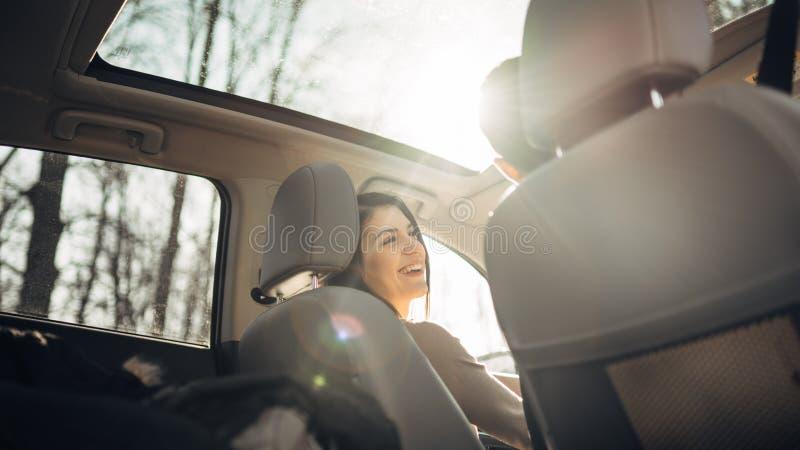 Mujer joven en un coche, un conductor femenino mirando el pasajero y la sonrisa Disfrutar del paseo, viajando, concepto del viaje foto de archivo libre de regalías