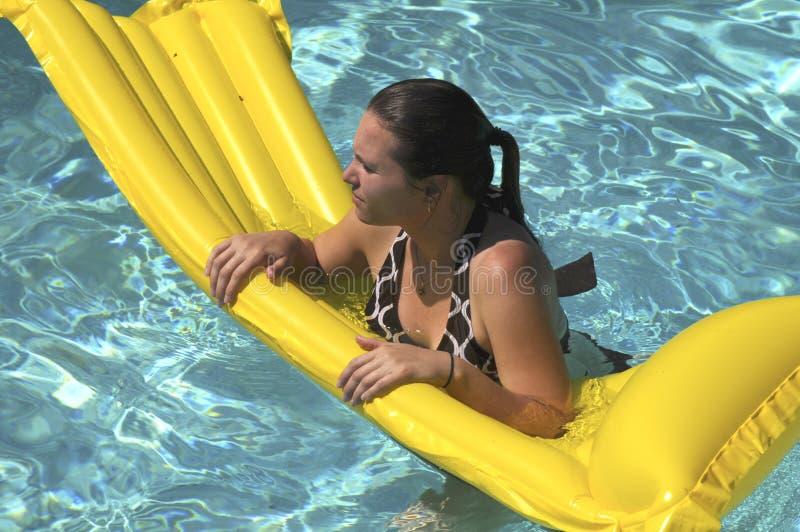 Mujer joven en un dispositivo de flotación que nada en una piscina fotografía de archivo