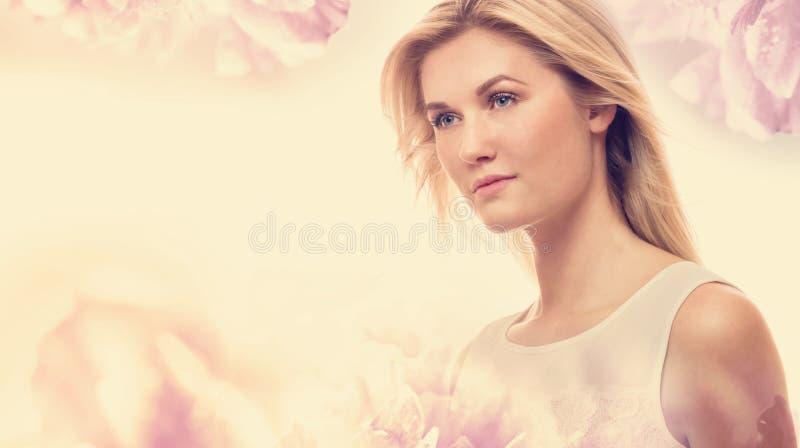 Mujer joven en un fondo floral rosado imágenes de archivo libres de regalías