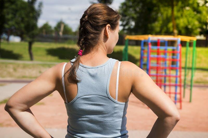 Mujer joven en un patio de los deportes en un día de verano brillante La muchacha va a jugar deportes y aptitud fotografía de archivo libre de regalías