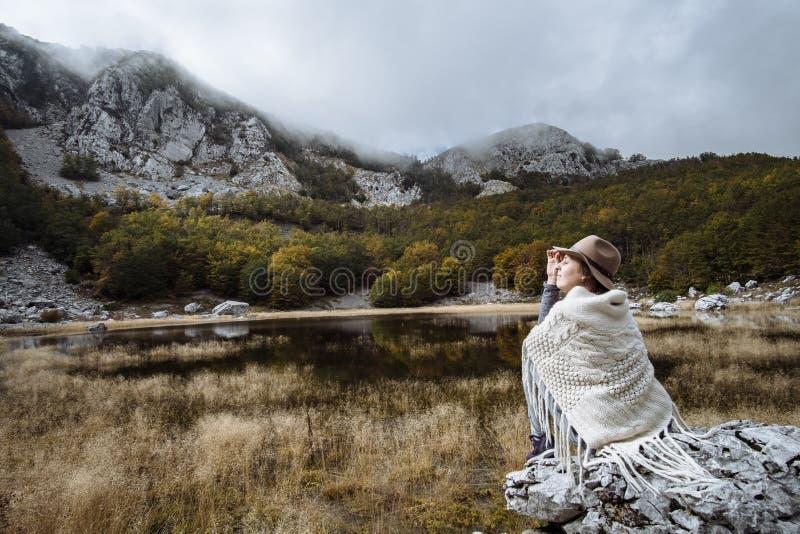 Mujer joven en un poncho y un sombrero que disfruta de la vista del lago, M fotografía de archivo