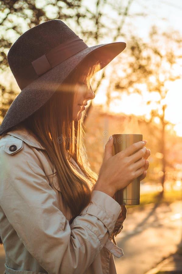 Mujer joven en un sombrero con el retrato al aire libre de la taza terma del termo en luz del día soleada suave Otoño Puesta del  fotografía de archivo libre de regalías