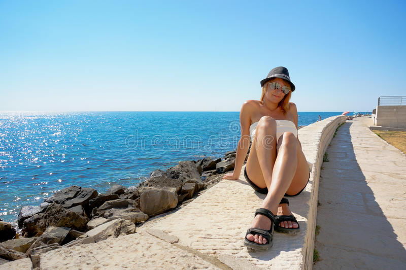 Mujer joven en un sombrero en el embarcadero cerca del mar. imágenes de archivo libres de regalías