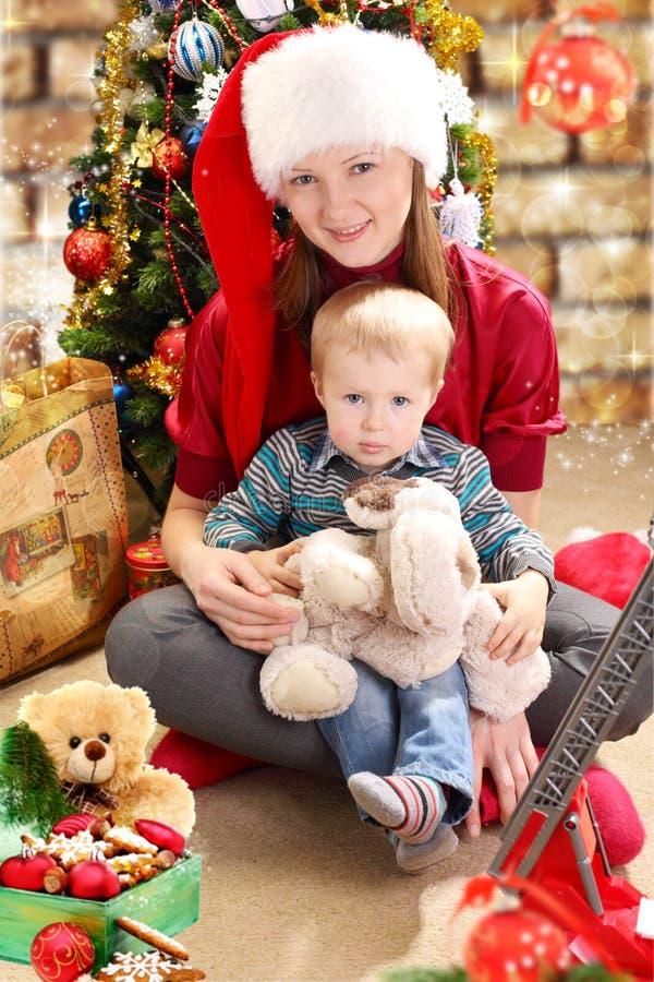 Mujer joven en un sombrero y un niño pequeño de Papá Noel. fotos de archivo
