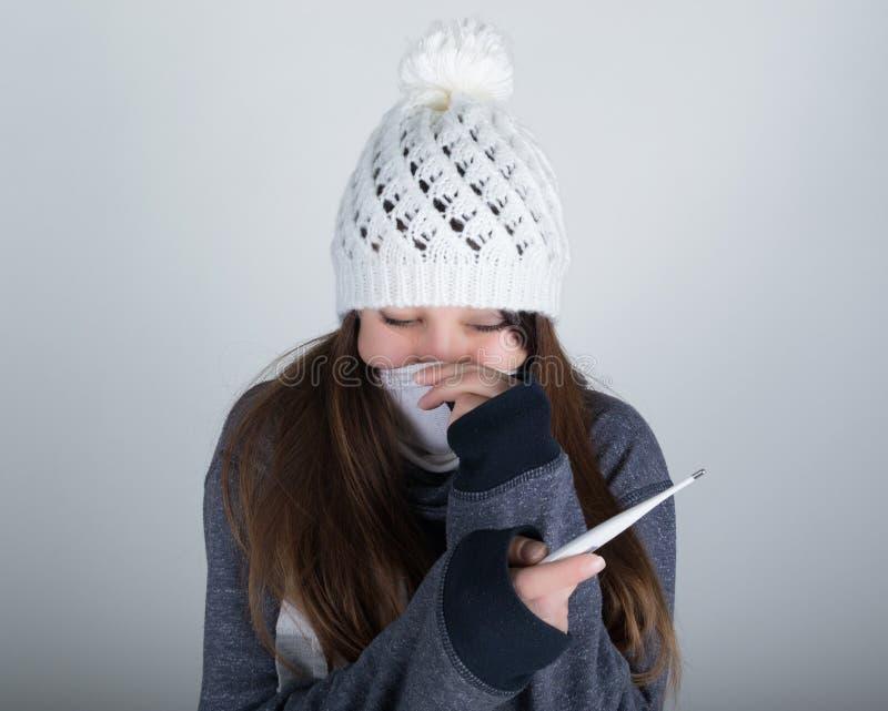 Mujer joven en un sombrero y una bufanda hechos punto, llevando a cabo las manos en el termómetro ella parece enferma foto de archivo