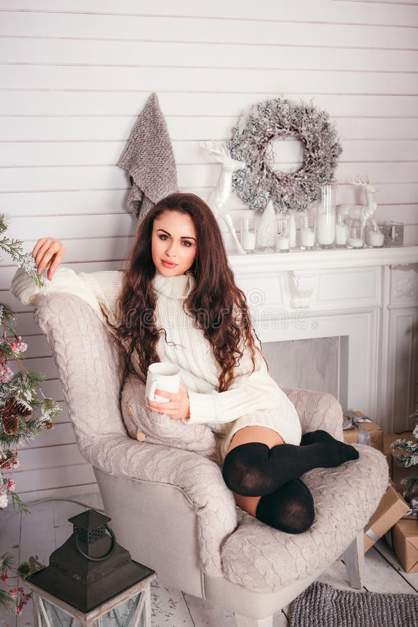 Mujer joven en un suéter caliente, sosteniendo un té caliente de la taza y de la bebida, imagen de archivo libre de regalías