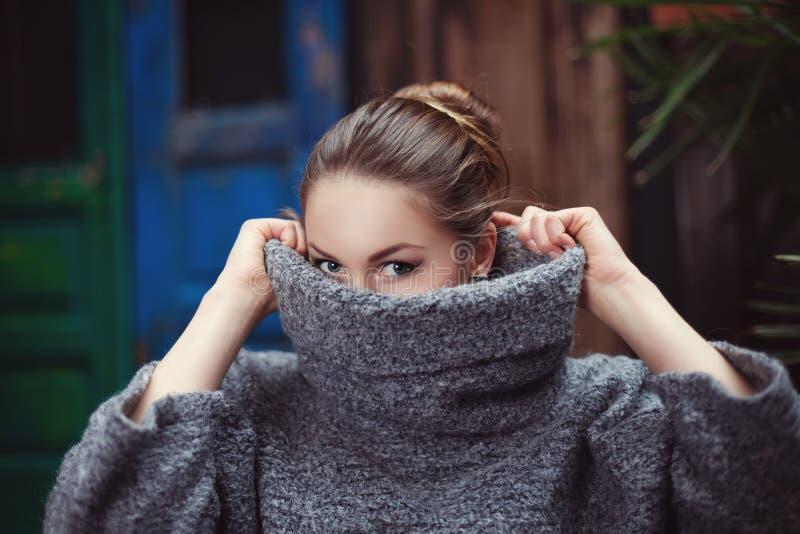 Mujer joven en un suéter hecho punto del cuello alto que cubre su cara Cierre para arriba imagenes de archivo