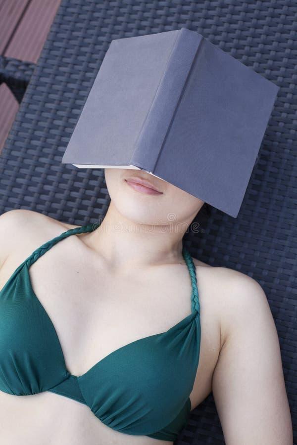 Mujer joven en un traje de baño que se acuesta y que se relaja con un libro sobre su cara imagen de archivo libre de regalías