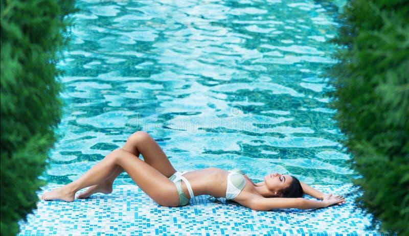 Mujer joven en un traje de baño que se relaja cerca de la piscina fotografía de archivo
