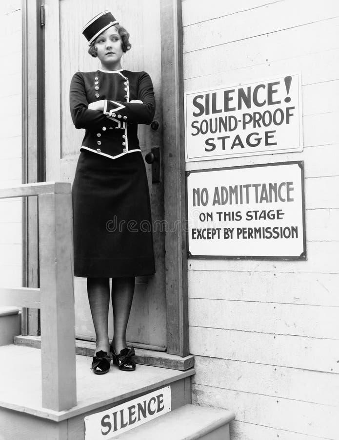 Mujer joven en un uniforme que se coloca con sus brazos cruzados delante de un a puerta cerrada (todas las personas representadas imagenes de archivo