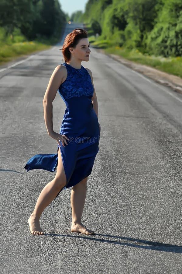 Mujer joven en un vestido azul en el camino imagen de archivo