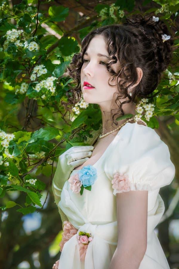 Mujer joven en un vestido blanco largo de la novia en árbol de las flores imagen de archivo libre de regalías
