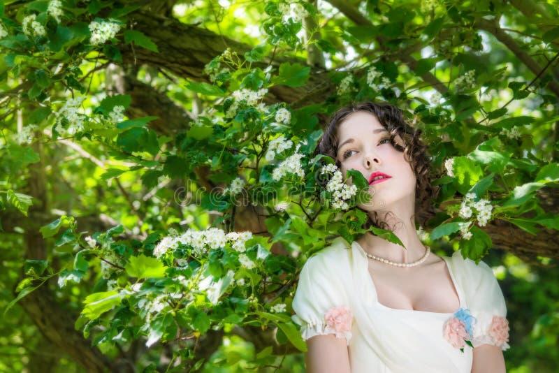 Mujer joven en un vestido blanco largo de la novia en árbol de las flores foto de archivo libre de regalías