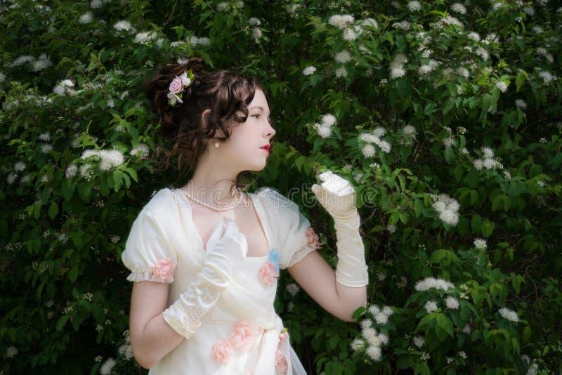 Mujer joven en un vestido blanco largo elegante de la novia en flores fotos de archivo libres de regalías
